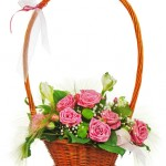 Colorful flower bouquet from roses in wicker basket  isolated on