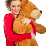 Happy woman hugging big teddy bear