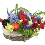 Flower arrangement of roses, orchids, fruits and bottle of wine.