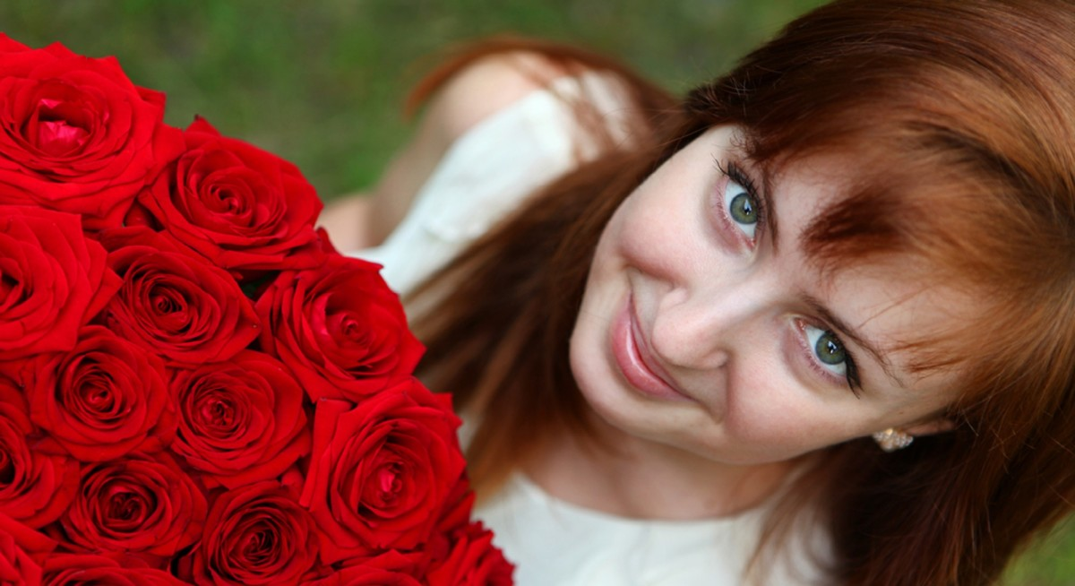 Beautiful young smiling woman with red roses