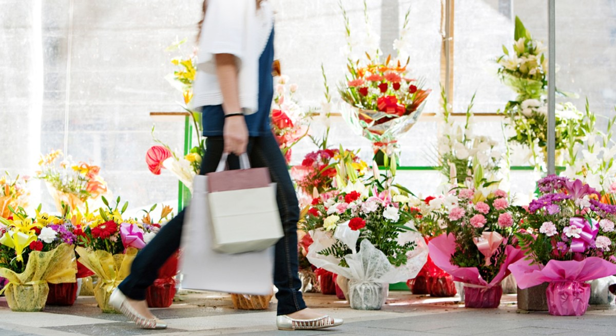 Side view of the lower body section of a young woman walking passed a fresh flowers market stall carrying a paper shopping bag during a sunny day outdoors. Faceless figure.